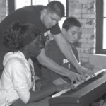 Piano instructor Zach Watson works with students Sira Sangare and Leo Dreis during a Live Soundz instrumental instruction session